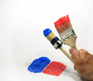Zwei Pinsel mit roter und blauer Farbe.